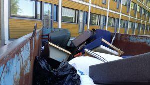 En fåtölj, säng och bokhylla är slängda på ett flak ned annat skräp utanför en studentbostad.