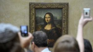 Människor trängs framför Mona Lisa i Louvren och tar bilder med sin mobil.