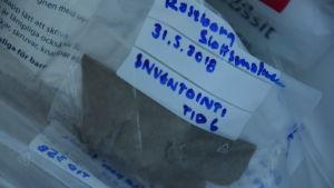En bild som visar hur arkeologer antecknar sina fynd. På bilden syns en plastpåse där det står Raseborg slottsmalmen 31.5.2018 inventointi.