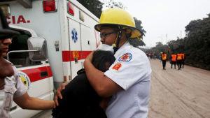 En brandman kramar Eufemia Garcia som förlorade sin familj i Eldvulkanens utbrott.