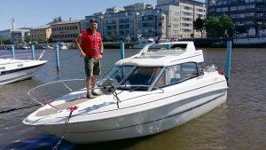 Kimmo Komulainen står i röd skjorta och beige shorts på sina båt Afrodite 2 i Aura å.