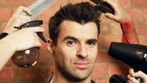 Mies katsoo kameraan samalla, kun hänen tukkaansa laitetaan eri välineillä.