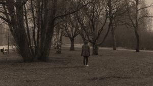 En person i jacka med huva står med ryggen mot kameran framför en träddunge i mörkt höstväder.