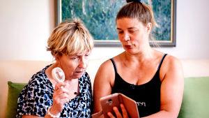 Digitaitojen opettamista älypuhelimella ikäihmiselle.