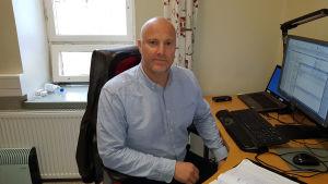 En man iklädd ljusblå skjorta sitter vid en dator. Han är i sitt kontor.
