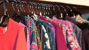 Färggranna kläder i vintagestil hänger på klädgalgar på ett kläräcke.