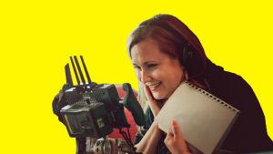 Anna Dahlman katsoo nauraen monitoriin, muuta työryhmää taustalla. Kuvaan lisätty grafiikkaa.