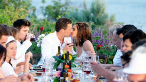 Nainen ja mies suutelevat pöydän päässä, viinilasit kädessä, muiden katsoessa.