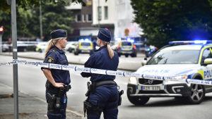 Två kvinnliga poliser bevakar ett avspärrat område. I bakgrunden står flera polisbilar.