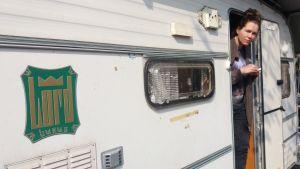 Kvinna tittar ut från husvagn