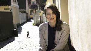 Programvärd Cecilie Nielsen sitter på huk vid en gata omgiven av gamla hus.