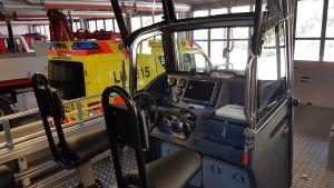 Förarhytten med ratt och två sittplatser i en öppen räddningsbåt.