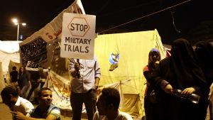 Folk protesterar mot den egyptiska militärdomstolen på Tahrirtorget i Kairo
