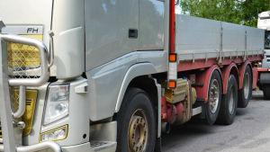 En bild på en silverfärgad lastbil med gula och röda detaljer. På bilden syns fyra däck och i bakgrunden träd.