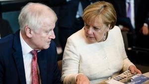 Inrikesminister Horst seehofer och förbundskansler Angela Merkel under parlamentsgruppens möte den 12 juni 2018.