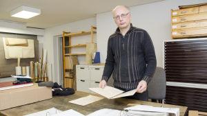 En man står i ett rum som är fyllt med arkiveringslådor och gamla papper. Han håller i ett gammalt handskrivet dokument.