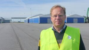 Patrik Hellman står med en gul väst på vid hamnen i Kaskö.