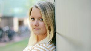 Michaela Rosenback ser in i kameran lutad mot en grå tegelvägg. Hon är klädd i en gul-vit randig t-skjort.