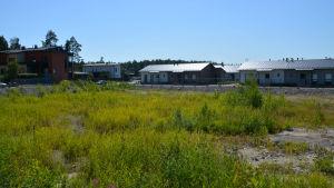 Radhus och våningshus intill ett vildväxt grusområde med staket runtomkring.