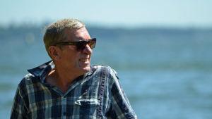 Peter Oljemark poserar i solglasögon, med havet i bakgrunden.