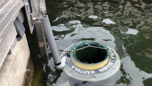 Seabin ligger förtöjd vid pontonbryggan.