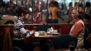 Kaksi naista istuu ravintolapöydän molemmin puolin.