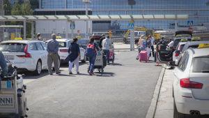 Matkustajat Helsinki-Vantaan lentoaseman taksitolpalla