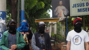 Fyra maskerade män framför kyrkan.