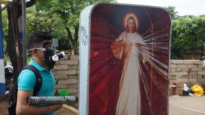 Kille med gasmask framför en Jesus-bild på gatan i Nicaraguas huvudstad.