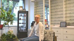 En kvinna sitter på en bänk framför en vägg med många glasögon.