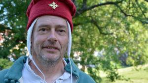Jaakko Nuotio klädd i en medeltida röd hatt.