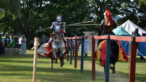 Två riddare rider mot varandra med lansarna sänkta.
