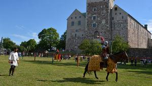 En riddare till häst och hans väpnare framför Åbo slott under ett tornerspel.
