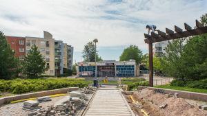 En avstängd park med trappor framför Mellugnsbacka metrostation. Parkens stenbeläggning är inte i skick, och det står högar av kakel i parken. En pojke klättrar på en träkonstruktion i parken.