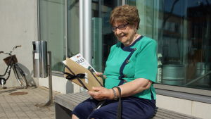 en äldre dam sitter utomhus på en bänk
