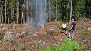 Två män bränner kvistar i skogen.