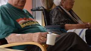 En äldre man som sitter och håller i en vit mugg.