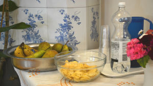 Ett bord dukat med frukt, chips och vatten.