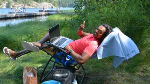 Man sitter i solstol med bärbar dator i famnen.