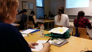 Studerande sitter i ett klassrum och svarar på skriftliga frågor.