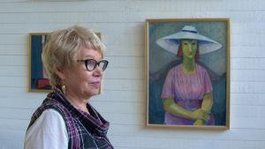 Kvinna står framför tavla av kvinna med grön hy.