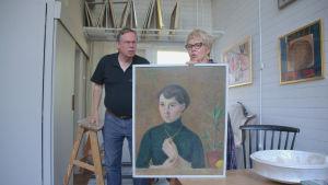 Porträtt av ung kvinna. En kvinna och en man står bakom porträttet.
