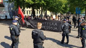En grupp demonstranter omringas av polisen på ett stentorg.