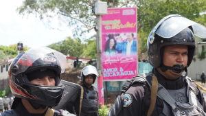 """Kravallpolis stoppar en fredlig demonstrations framfart. I bakgrunden affisch med president Daniel Ortegas och hustrun och tillika vicepresident Rosario Murillo. Deras budskap är: """"Kärlek till Nicaragua"""""""