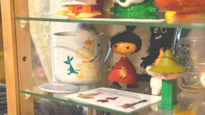En vit mugg med snorkfröken på i ett vitrinskåp.Bredvid står olika muminfigurer.