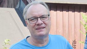 En man i blå t-skjorta ler mot kameran. Han har glasögon och kort hår.