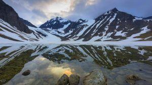 Kebnekaises två toppar med blå himmel i bakgrunden och en sjö i förgrunden.