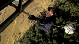 Ethan Hunt (Tom Cruise) klänger sig fast i ett rep under en helikopter.