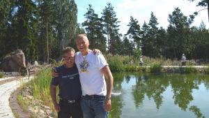 Två män står framför en liten damm.