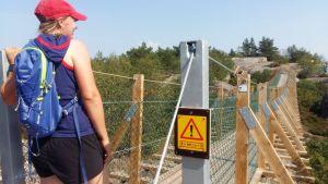 En dam med löpkläder, röd keps och en lätt ryggsäck står beredd att gå över en hängbro på Örö i Skärgårdshavets nationalpark. En gul skylt säger att det måste vara 5 meter mellan varje person som går över.